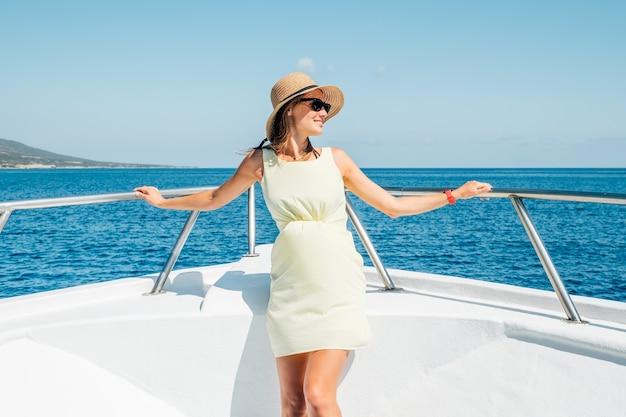 Giovane bella donna in piedi sullo yacht. viaggio di lusso in barca. vacanza in crociera