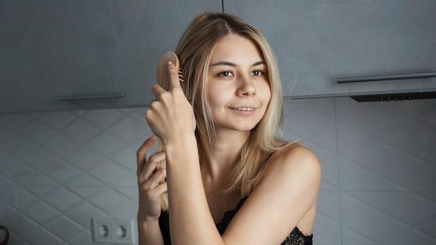 Giovane bella donna che raddrizza i suoi capelli biondi a casa