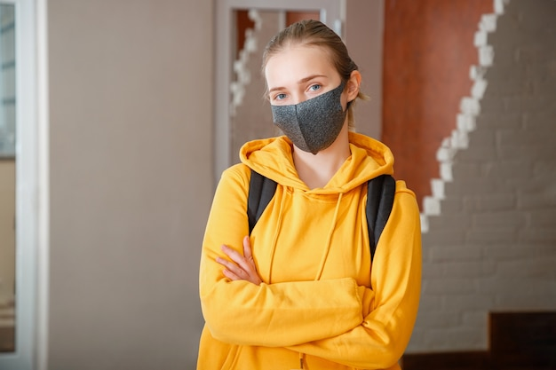 Giovane bella studentessa che indossa maschera protettiva con zaino. teen girl bionda adolescente viaggiatore caucasico con le braccia incrociate in maschera. studente felice nel lockdown del campus universitario riaprire il covid 19