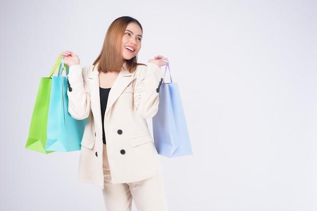 Giovane bella donna in vestito che tiene le borse della spesa colorate su sfondo bianco studio