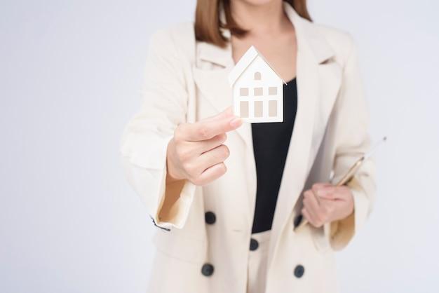 Giovane bella donna in vestito che tiene una piccola casa modello su sfondo bianco studio