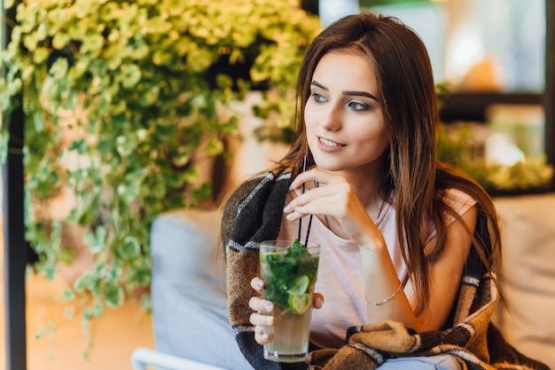Giovane bella donna su una terrazza estiva in abbigliamento casual sta bevendo un cocktail.