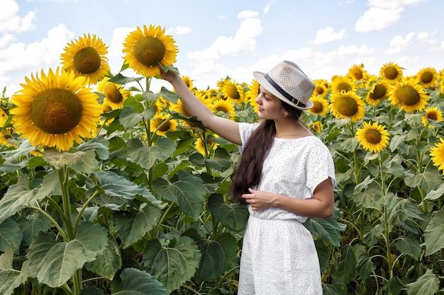 Giovane bella donna in un campo di girasoli