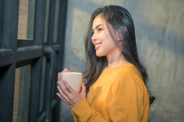 Una giovane bella donna alla luce del sole che gode del suo caffè del mattino a casa