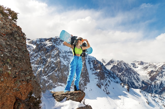 La giovane bella donna in costume da bagno con uno snowboard sulle sue spalle esamina il pendio della montagna