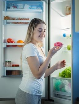 Giovane bella donna che prende la ciambella dal frigo a tarda sera