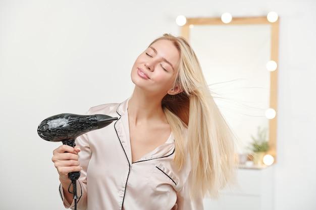 Giovane bella donna che prende piacere nell'aria calda durante l'utilizzo di asciugacapelli dopo aver lavato i suoi capelli biondi sani e spessi lunghi