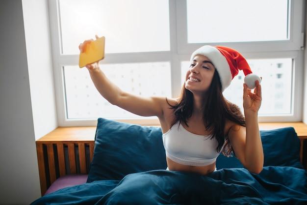 Giovane bella donna che cattura selfie indossando il cappello rosso di natale