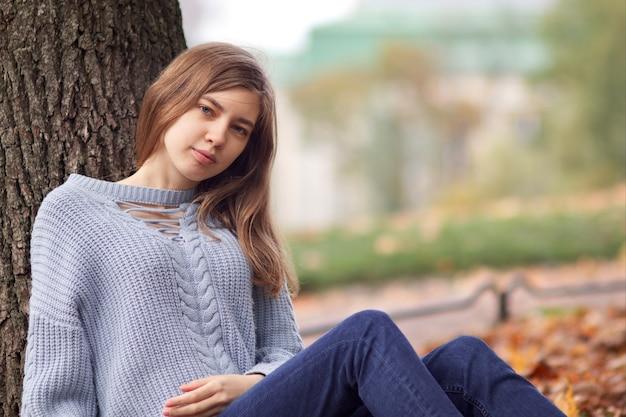 Giovane bella donna, ragazza dell'adolescente che si siede al parco dorato di autunno che si appoggia su un albero in maglione