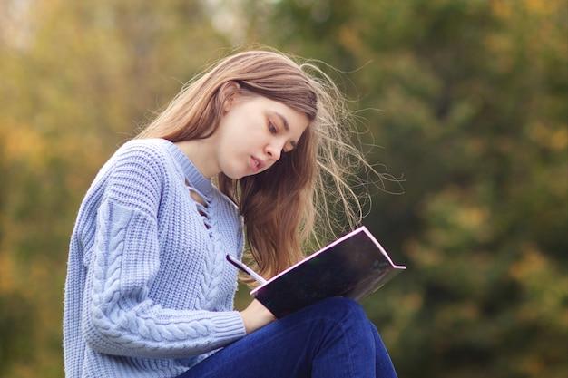Giovane bella donna, studente adolescente sta studiando all'aperto nel parco scrivendo in taccuino, con