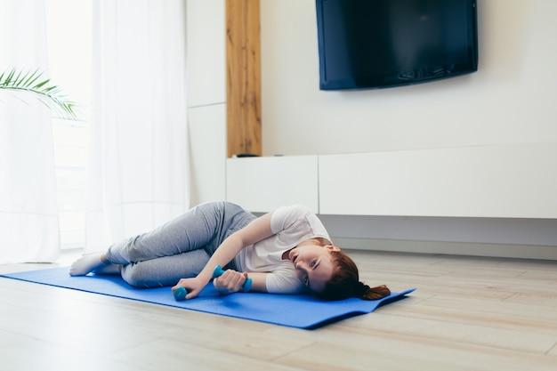 Giovane bella donna stanca dopo aver fatto fitness e ginnastica mattutina a casa