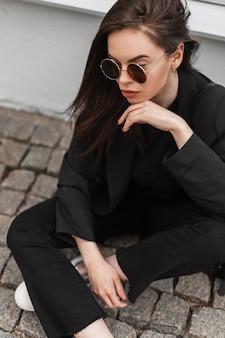 La giovane bella donna in occhiali da sole alla moda in vestiti neri freschi della gioventù sta riposando vicino all'edificio d'annata in città. la ragazza alla moda gode di un periodo di riposo su piastrelle di pietra sulla strada. abbigliamento moda primaverile per donna.