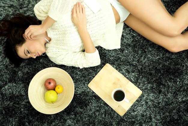 Una giovane bella donna in biancheria intima sdraiata su un tappeto e ascoltando musica
