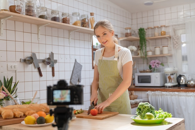 Giovane bella donna che utilizza la videocamera per registrare video come preparare un'insalata e preparare una panetteria per la pubblicazione sui social media nel suo canale cibo sano a casa cucina