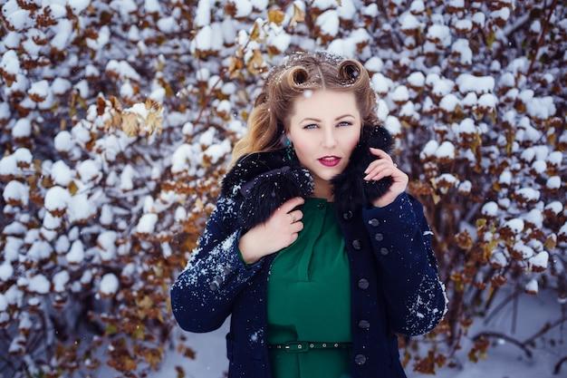 Giovane bella donna che cammina in un parco e respira aria fresca invernale e si sente meravigliosa. modello plus size
