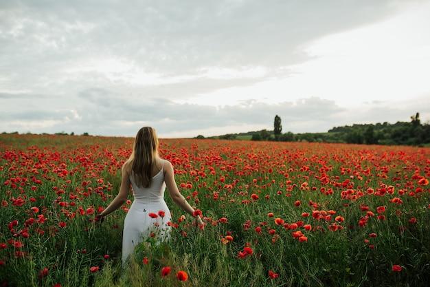 Giovane bella donna che cammina in un campo di papaveri