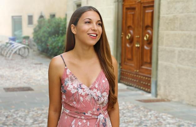 Giovane bella donna che cammina per le strade di una città italiana.