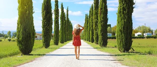 Giovane bella donna che cammina nella tipica strada in toscana