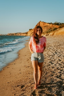 Una giovane bella donna cammina lungo la spiaggia e ammira il paesaggio marino al tramonto