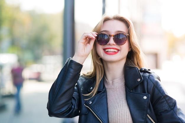 La giovane bella donna cammina per le strade della città tra l'edificio con gli occhiali da sole