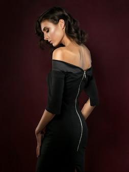 Giovane bella donna che indossa l'abito da sera nero in posa su sfondo rosso scuro