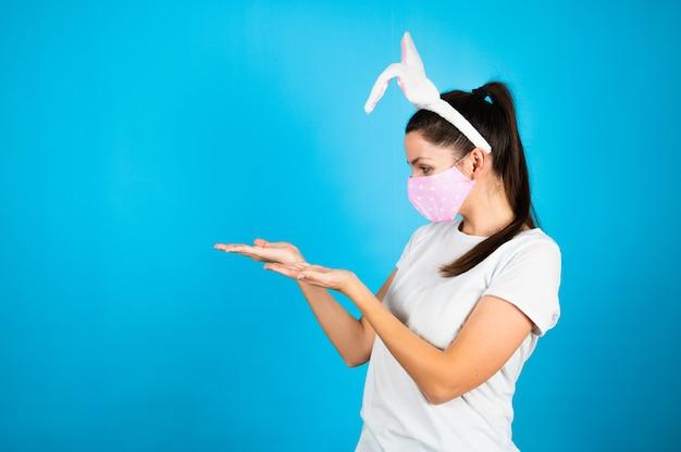 Giovane bella donna che indossa le orecchie di coniglio di pasqua in piedi sulla presentazione blu e indicando con i palmi della mano.