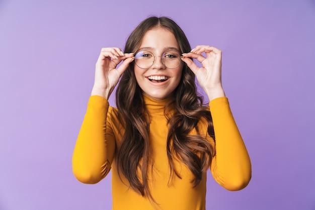Giovane bella donna che indossa occhiali sorridente e posa in telecamera isolata