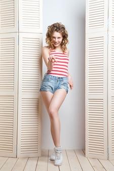 Giovane bella donna che indossa pantaloncini di jeans e top in posa davanti a una gelosia
