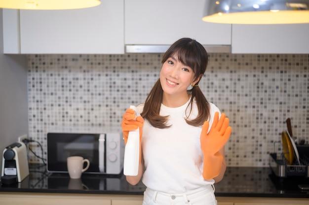 Una giovane bella donna che indossa guanti di gomma protettivi sta pulendo il tavolo in cucina a casa.