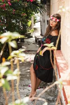 Giovane bella donna che indossa abito tradizionale messicano sulla strada della città Foto Premium