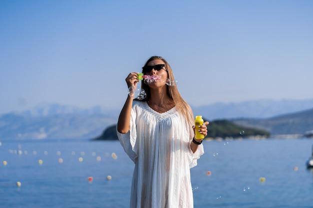 Giovane bella donna in vestito bianco ed occhiali da sole che soffiano le bolle di sapone sul pilastro con il fondo di vista del mare. il concetto di gioia, facilità e libertà durante le vacanze. la ragazza si sta godendo il resto.