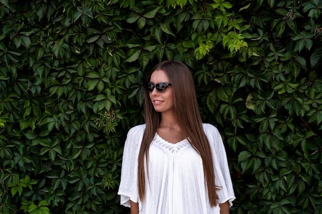 Giovane bella donna in vestito bianco ed occhiali da sole sul fondo verde del cespuglio. il concetto di gioia, facilità e libertà durante le vacanze. la ragazza si sta godendo il resto. foto di strada di moda.