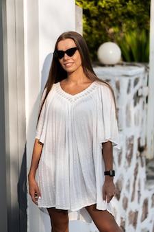 Giovane e bella donna in abito bianco e occhiali da sole si gira sulla strada con le palme. il concetto di gioia, facilità e libertà durante le vacanze. la ragazza si sta godendo il resto. moda
