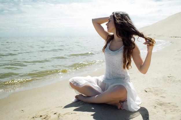 Una giovane bella donna in abito bianco cammina sulla spiaggia
