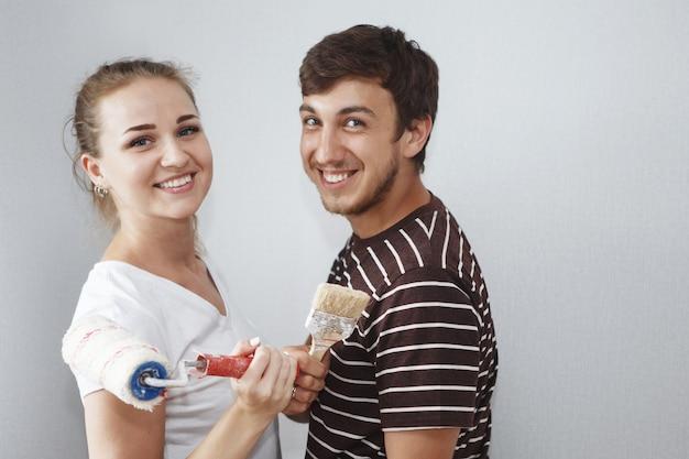 Giovane bella donna in maglietta bianca e ragazzo con la barba in posa con pennello e spatola nel nuovo appartamento durante la riparazione
