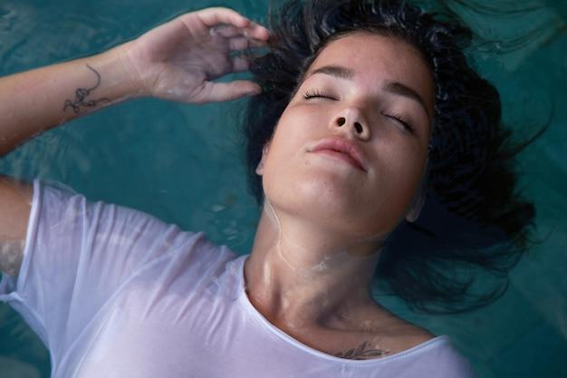 Giovane bella donna in una maglietta bianca in piscina tropici