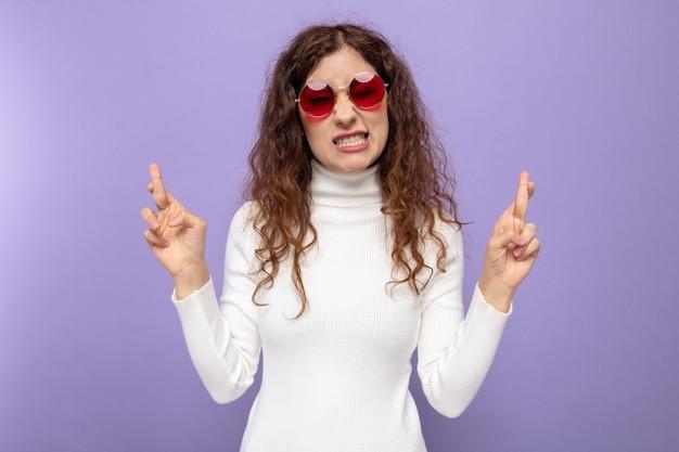 Giovane bella donna in dolcevita bianco che indossa occhiali rossi che esprime il desiderio desiderabile incrociando le dita con l'espressione di speranza in piedi sul viola