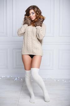 Giovane bella donna in vestiti caldi di inverno e calze bianche sulle luci