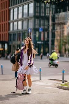 Giovane bella donna con lo zaino che posa alla macchina fotografica