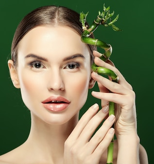 Giovane bella donna con bambù su sfondo verde, da vicino