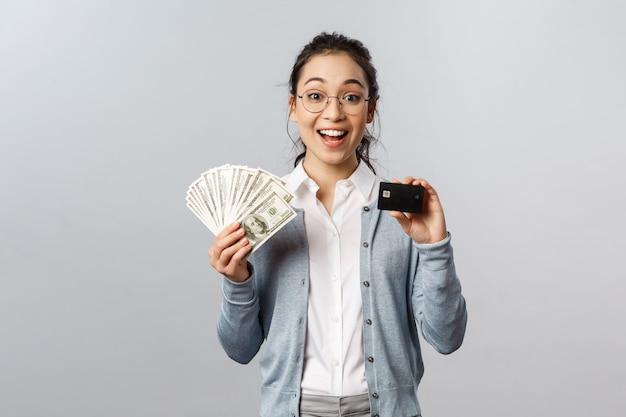 Giovane bella donna con carta di credito nera e denaro contante