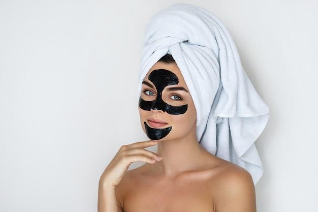 Giovane e bella donna con la maschera nera staccata sul viso