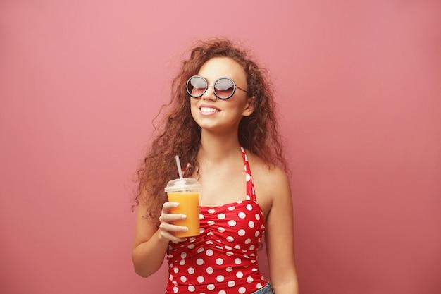 Giovane bella donna con cocktail sul colore