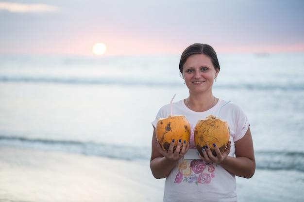 Giovane bella donna con noci di cocco al tramonto.