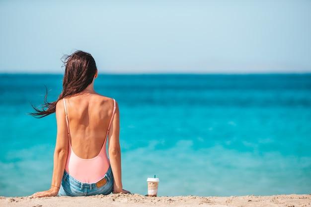 Giovane bella donna con caffè sulla spiaggia durante le vacanze estive tropicali