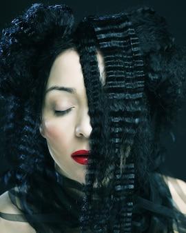 Giovane bella donna con capelli ricci e labbra rosse. ritratto di moda glamour.