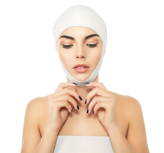Giovane bella donna con una fasciatura elastica sulla sua testa, isolata su white