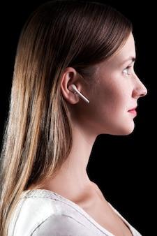 Giovane bella donna con lentiggini e auricolari wireless sulle orecchie. girato in studio su sfondo nero..