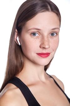 Giovane bella donna con lentiggini e auricolari wireless sulle orecchie. girato in studio.