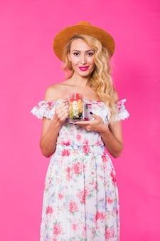 Giovane bella donna con vaso di frutta sulla parete rosa